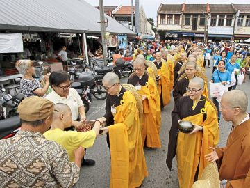 Devotees offering food alms and money to the novice monks and nuns during a procession from Penang Buddhist Association in Anson Road to Kek Lok Si Temple in Air Itam, Penang./Picby:CHAN BOON KAI/1 December 2019.